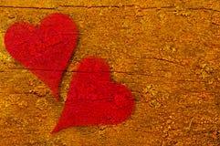 Dois corações vermelhos fundidos com o fundo de madeira abstrato fotos de stock royalty free