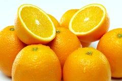 Dois cortaram laranjas suculentas entre o grupo de laranjas Imagens de Stock Royalty Free