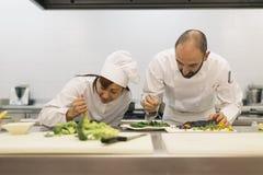 Dois cozinheiros chefe dos profissionais que cozinham junto fotos de stock