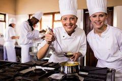 Dois cozinheiros chefe fêmeas que preparam o alimento na cozinha foto de stock