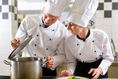 Dois cozinheiros chefe na equipe na cozinha do hotel ou do restaurante Fotografia de Stock Royalty Free