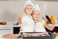 Dois cozinheiros chefe pequenos que mostram os polegares acima Imagens de Stock Royalty Free