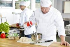 Dois cozinheiros chefe profissionais que preparam o alimento na grande cozinha fotografia de stock royalty free