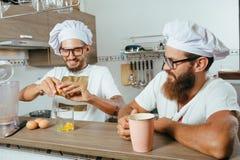 Dois cozinheiros chefe que cozinham na cozinha Fotos de Stock