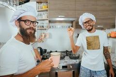 Dois cozinheiros chefe que cozinham na cozinha Imagens de Stock