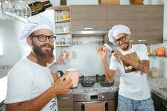 Dois cozinheiros chefe que cozinham na cozinha Fotografia de Stock Royalty Free