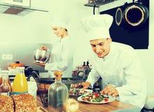 Dois cozinheiros chefe que cozinham o alimento fotografia de stock royalty free