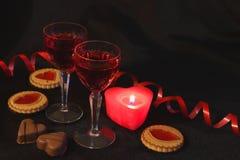 Dois cristais do vinho, das velas e dos doces Vermelha é a cor da paixão Tâmara romântica Seja meu Valentim imagem de stock royalty free