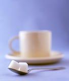 Dois cubos do açúcar com uma chávena de café em um saucer Fotografia de Stock Royalty Free