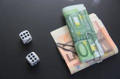 Dois dados com os pacotes de dinheiro com fundo preto Fotografia de Stock Royalty Free
