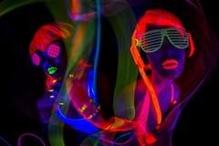 Dois dançarinos uv de néon 'sexy' do fulgor imagem de stock