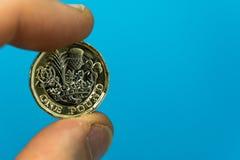 Dois dedos que guardam a moeda de libra BRITÂNICA nova em um fundo azul Fotos de Stock Royalty Free