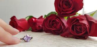 Dois dedos que tocam no anel de prata do desenhista com a gema violeta grande fotografia de stock royalty free