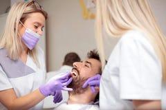Dois dentistas fêmeas novos que trabalham na clínica dental Clareando os dentes pacientes masculinos e a utilização da carta do t imagens de stock royalty free