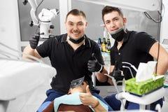 Dois dentistas masculinos no uniforme preto estão mostrando os polegares acima e estão sorrindo à câmera foto de stock royalty free