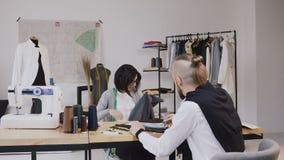 Dois desenhadores de moda dos povos que escolhem a tela no escritório com as ferramentas e roupa de costura diferentes Jovem mulh filme
