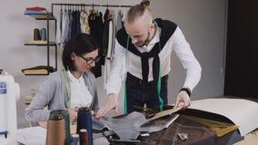 Dois desenhadores de moda multi-étnicos dos povos que trabalham com testes padrões e telas no escritório bonito com diferente video estoque
