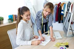 Dois desenhadores de moda novos que decidem nos projetos da coleção nova da roupa na oficina costurando fotos de stock royalty free