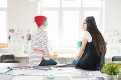 Dois desenhadores de moda que conversam no trabalho imagem de stock royalty free