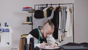 Dois desenhadores de moda que trabalham para sua coleção nova Os pares de desenhadores de moda estão trabalhando na oficina styli filme