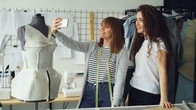 Dois desenhistas fêmeas criativos estão fazendo o selfie com telefone esperto ao estar ao lado de costurar o manequim no local de video estoque