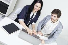 Dois desenhistas ocasionais de sorriso que trabalham com portátil e tabuleta no escritório Trabalhos de equipa do wooman do homem Imagens de Stock