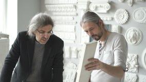 Dois designer de interiores masculinos maduros que discutem o emplastro branco vídeos de arquivo