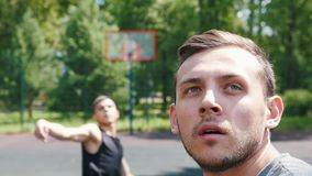 Dois desportistas que jogam o basquetebol no ar livre da corte - um homem que joga a bola - o outro homem que olha o vídeos de arquivo