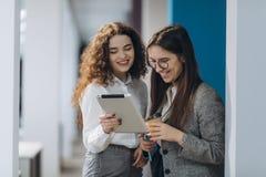 Dois diretores administrativos fêmeas que discutem ideias do projeto na tabuleta digital ao andar para baixo no salão do escrit foto de stock