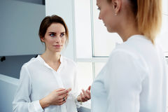 Dois diretores administrativos fêmeas que falam sobre algo pessoal ao estar no corredor do interior moderno do escritório, Fotos de Stock Royalty Free