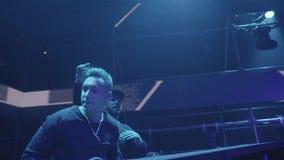 Dois DJ com um equipamento do misturador no clube noturno video estoque
