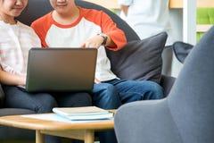 Dois dos estudantes adolescentes asiáticos que estudam junto no sofá no libra Fotos de Stock