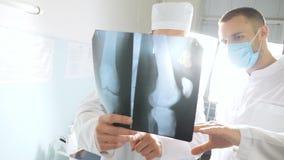 Dois doutores caucasianos veem a imagem do mri e a discussão sobre ela Os médicos masculinos consultam um com o otro ao olhar x filme
