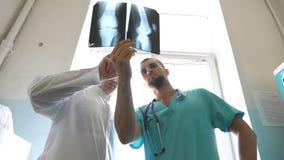 Dois doutores caucasianos veem a imagem do mri e a discussão sobre ela Os trabalhadores médicos no hospital examinam cópias do ra filme