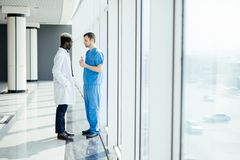 Dois doutores da raça misturada que discutem o diagnóstico ao andar no hospital fotos de stock royalty free