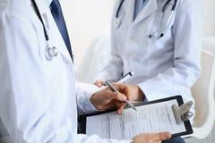Dois doutores desconhecidos que enchem-se acima do formulário médico na prancheta, apenas close up das mãos Médicos que fazem a p fotos de stock royalty free