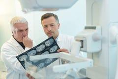 Dois doutores do yound que examinam o filme de raio X no diafanoscópio Imagem de Stock