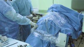 Dois doutores e enfermeira durante a cirurgia laparoscopic video estoque