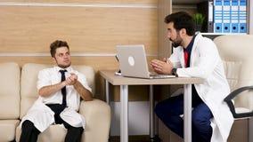 Dois doutores masculinos no escritório moderno que falam sobre casos médicos filme