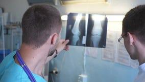 Dois doutores masculinos veem a imagem do mri e a discussão sobre ela Trabalhadores médicos na vista do hospital e no raio X anal vídeos de arquivo