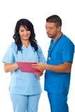 Dois doutores que lêem a prancheta Imagem de Stock