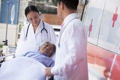 Dois doutores que rodam em um paciente idoso em uma maca na frente de uma ambulância Imagem de Stock