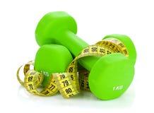 Dois dumbells e fitas métricas verdes Aptidão e saúde foto de stock royalty free
