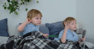Dois 4 e 2 anos dos meninos, velho, estão olhando a tevê sentar-se no sofá Um programa televisivo emocionante Desenhos animados d