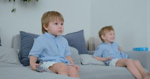 Dois 4 e 2 anos dos meninos, velho, est?o olhando a tev? sentar-se no sof? Um programa televisivo emocionante Desenhos animados d