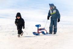 Dois 8 e 4 anos dos meninos, velho, vão com os trenós na neve branca pura foto de stock