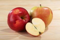 Dois e umas meias maçãs maduras e suculentas da cor vermelha e verde em uma tabela de madeira Close-up Foto de Stock