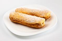 Dois eclairs no prato branco Imagem de Stock