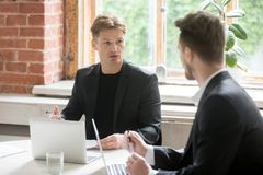 Dois empregados executivos que discutem objetivos incorporados na frente de l Foto de Stock Royalty Free