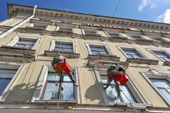 Dois empregados suspenderam em uma altura de lavar Windows fotos de stock